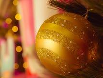 Nahaufnahme, die der dekorative einzelne goldene Weihnachtsball mit de-fokussiertem bokeh beleuchtet Stockfotografie