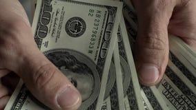 Nahaufnahme - die Hände der Männer, die aus Dollarscheinen zählen stock footage