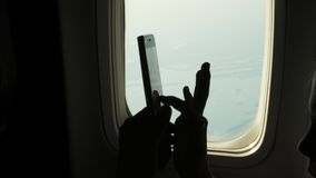 Nahaufnahme dunkles Schattenbild von Kinderhänden und -Handy gegen die Belichtungseinheit des Flugzeuges An verwendendes Kind, Sp stock video