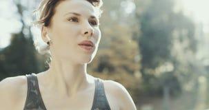 Nahaufnahme-Eignungsmädchen, das in drahtlose Kopfhörer des Ohrs sich setzt Frauenläufer des weiblichen Athleten tragende airpods lizenzfreie stockfotos