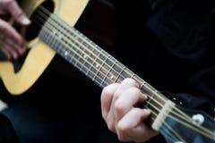 Nahaufnahme Ein Mann, der eine Akustikgitarre der Sechsschnur spielt verwischt stockfotografie