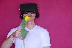 Nahaufnahme - ein Mann mit Gl?sern virtueller Realit?t gibt eine Tulpe lizenzfreie stockbilder
