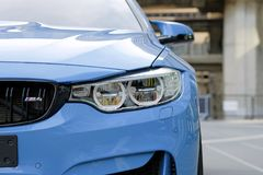 Nahaufnahme ein Scheinwerfer des Sport-Blauautos BMWs M4 Stockfotografie