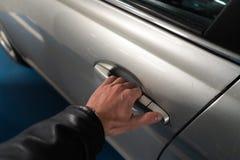 Nahaufnahme eine Hand der Männer auf der Klinke eines Autotüreinstiegs es herauf - helle Farbauto lizenzfreie stockfotografie
