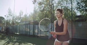 Nahaufnahme eine junge Dame, die das Tennis sehr Berufs, sonnigen Tag, tenu Gericht spielt Geschossen auf rotem Epose stock footage