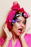 Nahaufnahme einer überraschten jungen Frau mit Haarlockenwicklern Stockfotos
