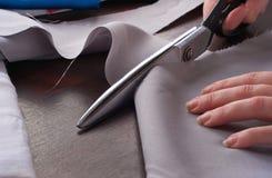 Nahaufnahme einer Damenschneiderin schneidet Scherenstoff stockfoto