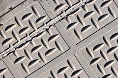 Nahaufnahme einer diagonalen grauen Straßenabdeckung lizenzfreie stockfotografie