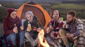 Nahaufnahme einer Firma von vier kaukasischen jungen Freunden, die ein Picknick durch die Berge haben, plaudern sie und lachen stock video