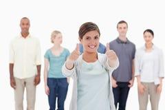 Nahaufnahme einer Frau, die die Daumen-oben mit Leute beh gebend lächelt Lizenzfreies Stockfoto
