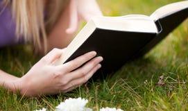Nahaufnahme einer Frau, die ein Buch in einem Park liest lizenzfreie stockfotografie