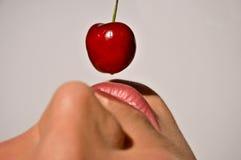 Nahaufnahme einer Frau, die eine Kirsche schmeckt Lizenzfreies Stockfoto