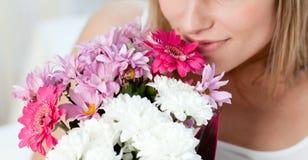 Nahaufnahme einer Frau, die einen Blumenstrauß riecht stockfoto