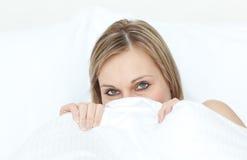 Nahaufnahme einer Frau, die in ihrem Bett versteckt Stockbilder