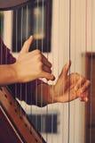 Nahaufnahme einer Frau, welche die Harfe spielt Stockfotos