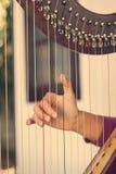 Nahaufnahme einer Frau, welche die Harfe spielt Lizenzfreie Stockfotografie