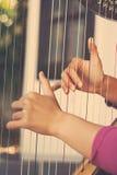 Nahaufnahme einer Frau, welche die Harfe spielt Lizenzfreies Stockbild