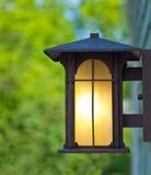 Nahaufnahme einer glühenden Lampe außerhalb eines hölzernen Gebäudes im Sommer Lizenzfreie Stockfotografie