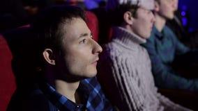 Nahaufnahme einer Gruppe Freunde, die einen traurigen Film in einem Kino aufpassen stock footage