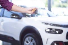 Nahaufnahme einer Hand, die Autoschlüssel mit einem unscharfen Auto im Ba hält stockbild