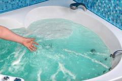 Nahaufnahme einer Hand, die das Wasser im Jacuzzi berührt Lizenzfreies Stockbild