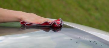 Nahaufnahme einer Hand, die ein Autoglas mit einem roten Lappen abwischt Lizenzfreie Stockbilder