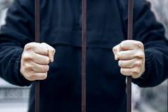 Nahaufnahme einer Hand, die einen Stahlk?fig, Gefangenkonzept h?lt H?nde des Gefangenen im Gef?ngnis Hoffnung, frei zu sein lizenzfreies stockfoto
