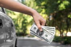 Nahaufnahme einer Hand, die Geld hält Fahren des Mannes, der Hunderte von den Dollar auf einem unscharfen grünen Hintergrund hält Stockbild