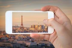 Nahaufnahme einer Hand mit dem Smartphone, der ein Foto von Paris mit dem Eiffelturm bei Sonnenuntergang Frankreich macht Lizenzfreies Stockfoto