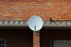 Nahaufnahme einer Hausmauer mit Sonnenkollektoren und der Satellitenschüssel mit Antenne Fernsehen lizenzfreie stockfotos