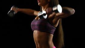Nahaufnahme einer jungen Frau, die mit Gewichten in der Turnhalle trainiert