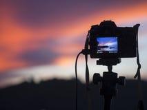 Nahaufnahme einer Kamera auf einem Stativ draußen Hintergrund-Landschaft unscharf Stockbild