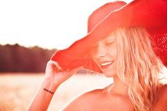 Nahaufnahme einer lächelnden jungen Frau, die mit einem Hut aufwirft Lizenzfreie Stockfotografie