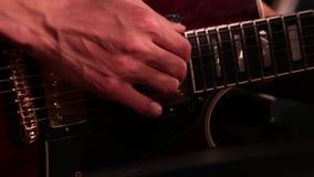 Nahaufnahme einer männlichen Hand beim Spielen einer E-Gitarre stock footage