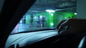 Nahaufnahme einer menschlichen Hand auf einem Armaturenbrett, bei der Aufwartung in ein geschlossenes Parken in einem Supermarkt  stock footage