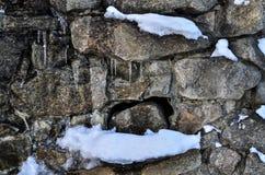 Nahaufnahme einer schneebedeckten eisigen Backsteinmauer mit einem weichen Hintergrund stockfotos