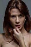Nahaufnahme einer sommersprossigen Frau, die ihre Lippe hält Stockfotografie