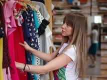 Nahaufnahme einer starken Frau, die im Bekleidungsgeschäft steht und nach einem Kleid auf einem unscharfen Hintergrund sucht Lizenzfreie Stockfotografie