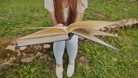 Nahaufnahme einer Studentin, die ein Buch, sitzend auf Gras unter einem großen Stadion liest Vorbereitung für Studie stock video footage