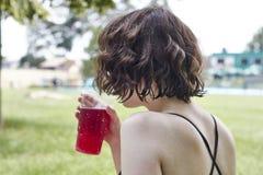 Nahaufnahme einer trinkenden Limonade des Mädchens mit unscharfem Swimmingpool I lizenzfreies stockfoto