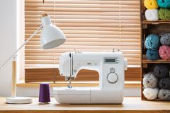 Nahaufnahme einer weißen Nähmaschine mit einem purpurroten Thread und Kisten mit Garn durch ein Fenster in einem hellen Handwerks stockfotografie