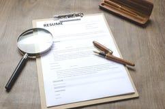 Nahaufnahme einer Zusammenfassungsanwendung, Klemmbrett, Stift, Vergrößerungsglas auf Holztisch, arbeitende Prozess-anstellende n stockbilder