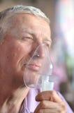Alter Mann mit einem Inhalator stockfotos