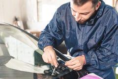 Nahaufnahme eines Berufswindschutzscheibenschlossers, der mit hydraulischem Polymersprungsfüller arbeitet Beseitigung von Sprünge stockbild