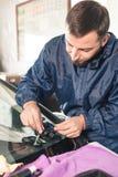 Nahaufnahme eines Berufswindschutzscheibenschlossers, der mit hydraulischem Polymersprungsfüller arbeitet Beseitigung von Sprünge lizenzfreie stockfotografie
