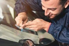 Nahaufnahme eines Berufswindschutzscheibenschlossers füllt einen Sprung im Glas mit einem speziellen Polymer durch eine Spritze lizenzfreie stockfotografie