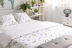 Nahaufnahme eines Betts kleidete des Grünpflanze-Musters der Biobaumwolle im weißen Leinen in einem sonnigen Schlafzimmerinnenrau lizenzfreie stockfotos