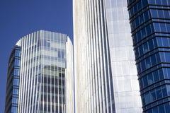Nahaufnahme eines blauen Unternehmensgebäudes vor seinem Doppelgebäude Stockfotos