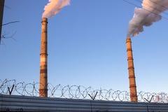 Nahaufnahme eines einzelnen konkreten Schornsteins, der in den dunkelblauen Himmel mit dem türmenden Rauche steigt stockbild