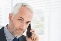 Nahaufnahme eines ernsten reifen Geschäftsmannes unter Verwendung des Mobiltelefons stockfotografie